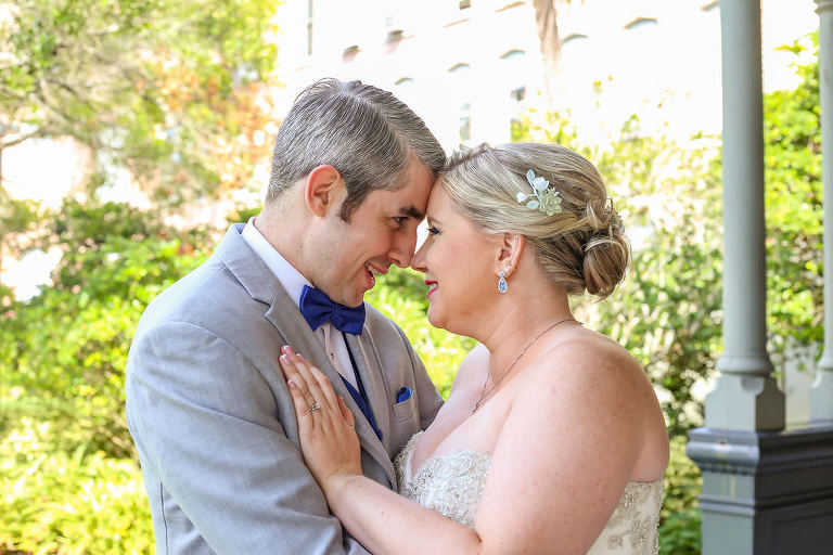 Florida Bride and Groom Outside Wedding Portrait, Bride Wearing Rhinestone Hair Clip with Updo Bridal Hairstyle, Groom in Light Gray and Bold Blue Tuxedo