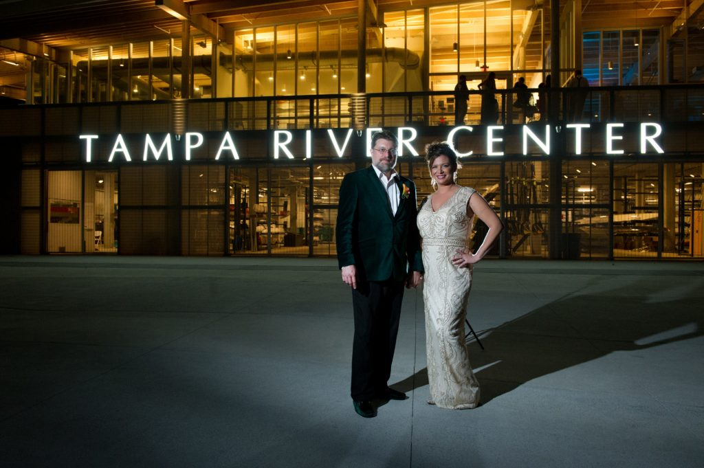 Tampa Bay Bride and Groom in Nighttime Wedding Portrait In Front of Exterior of Tampa River Center in Downtown Tampa at Night, Bride in Ivory Wedding Dress with Gold Detailing, Groom in Emerald Green Velvet Jacket | Tampa Bay Wedding Photographer Andi Diamond Photography| Tampa Bay Wedding Makeup Artist Michelle Renee the Studio