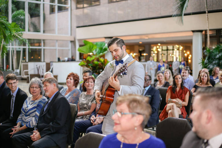 Groomsman during Ceremony Playing Guitar Down the Aisle for Processional, Groomsman Wearing Light Gray and Bold Blue Tuxedo, Indoor Ceremony at Night with Palm Trees | Tampa Bay Wedding Venue Tampa Centre Club