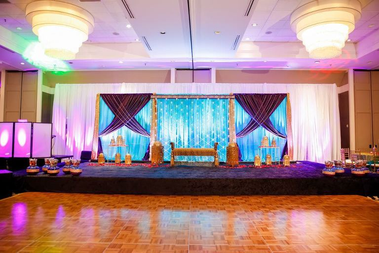 Elegant Colorful Traditional Indian Tampa Wedding | White, Blue and Purple Linen Backdrop with Purple Uplighting, Gold Furniture Accents | Hotel Ballroom Wedding Venue Hilton Tampa Airport Westshore