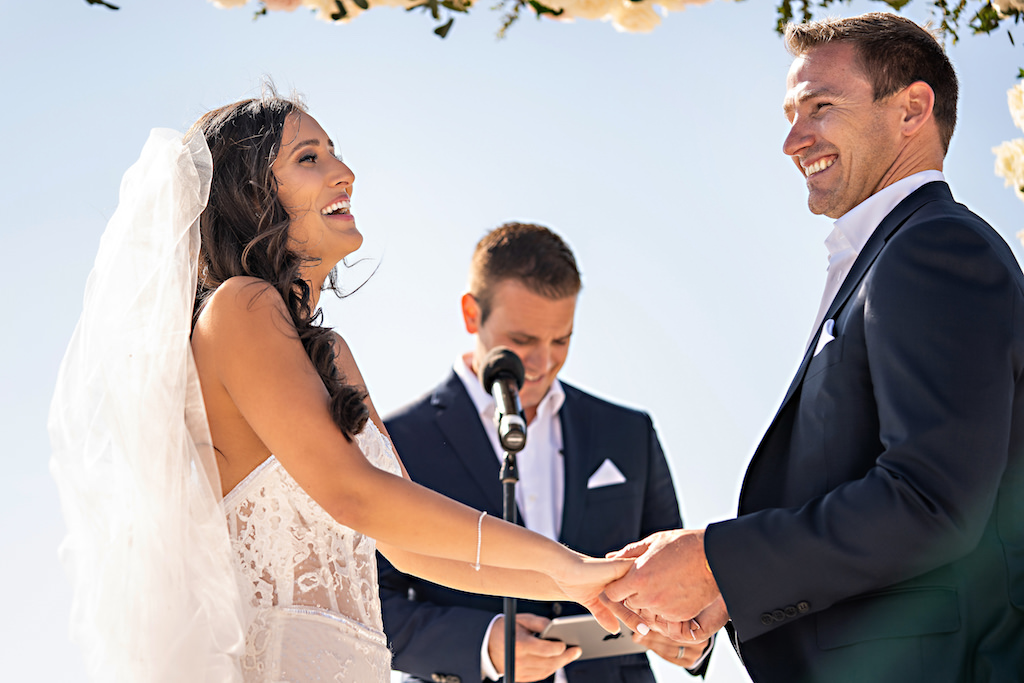Florida Bride and Groom Hold Hands During Romantic Wedding Ceremony