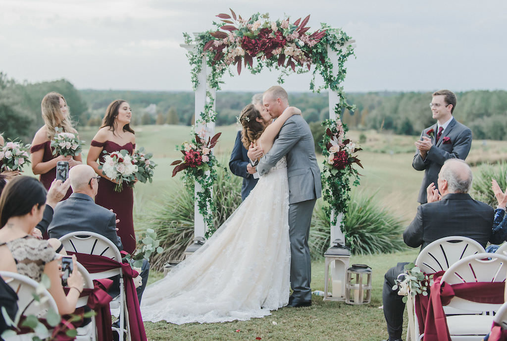 Florida Bride and Groom Kiss During Rustic Chic Outdoor Wedding Ceremony, Under White Arch with Burgundy, Blush Pink and White Floral Arrangements with Greenery | Brooksville Golf Course Southern Hills Plantation | Tampa Bay Bridal Shop Nikki's Glitz and Glam Boutique