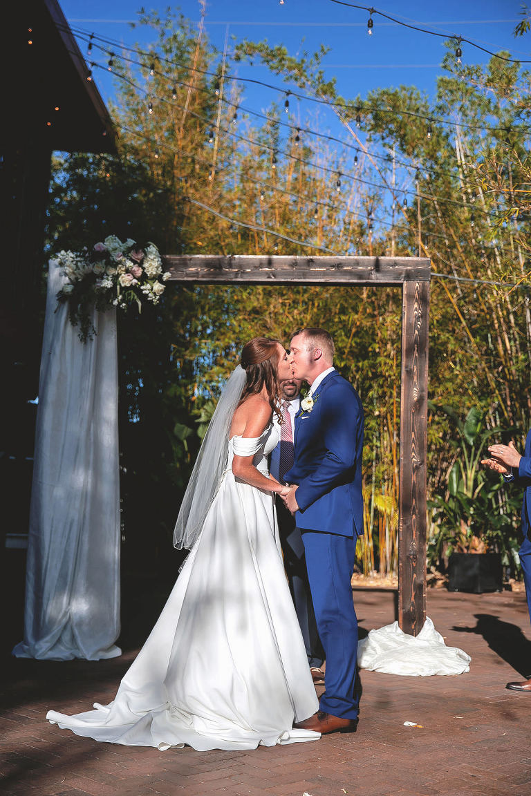 Tampa Bay Bride and Groom First Kiss under Wooden Ceremony Arch in Downtown St. Pete Bamboo Garden | Florida Unique Wedding Venue NOVA 535