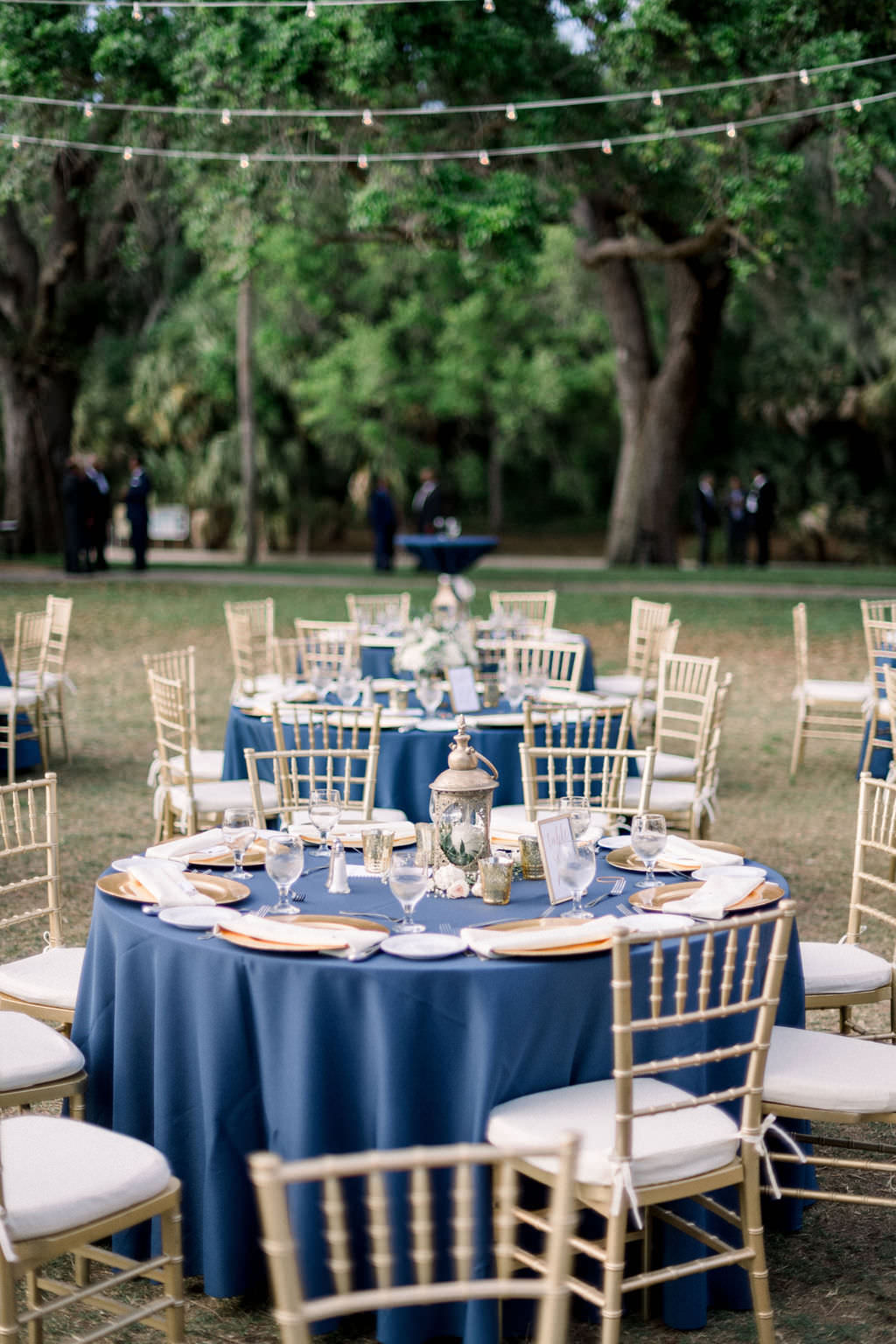 Elegant, Vintage Inspired Outdoor Wedding Decor and Reception, Navy Blue Table Linens, Gold Chargers, Chivari Chairs, Low Centerpiece Lantern, at Powel Crosley Estate | Sarasota Wedding Planner Laura Detwiler Events