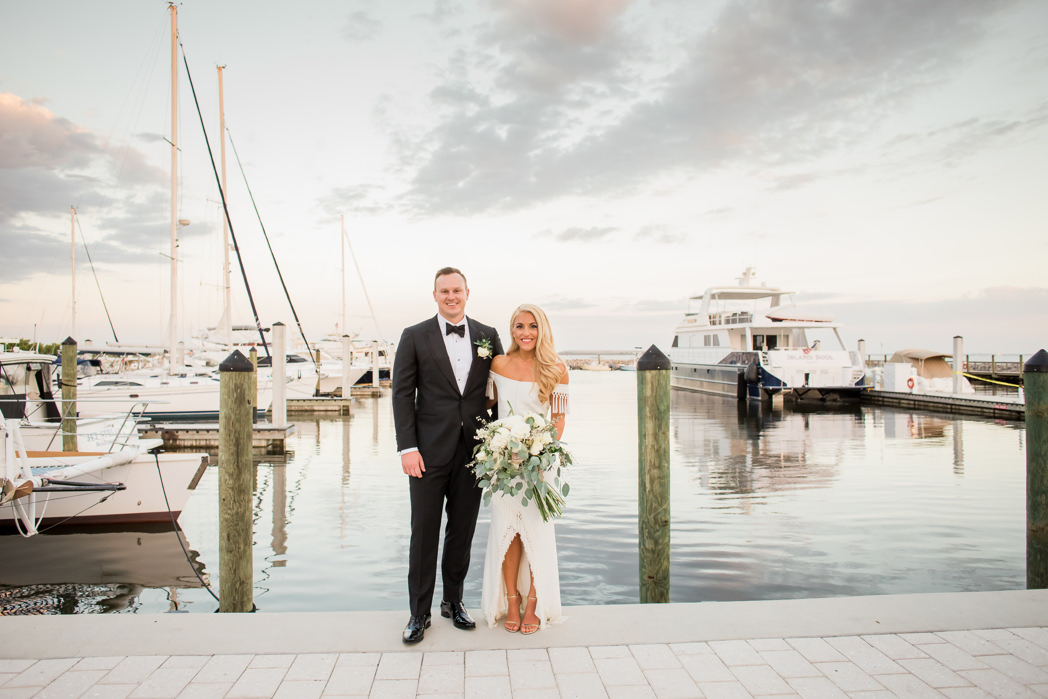 South Tampa Florida Bride Holding Organic White, Ivory, Blush Pink Floral and Greenery Bouquet and Groom on Waterfront Boat Dock During Sunset | Wedding Venue Tampa Yacht and Country Club | Tampa Bay Wedding Hair and Makeup Artist LDM Beauty Group