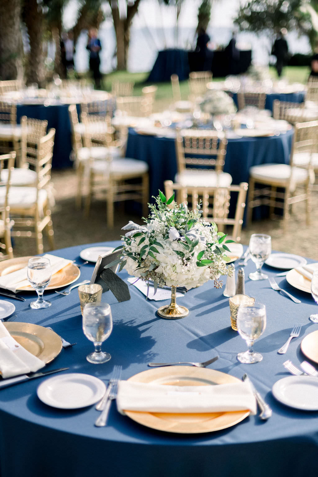 Elegant, Vintage Inspired Wedding Decor, Outdoor Reception, Navy Blue Table Linens, Gold Chargers, Low Floral Centerpiece, White and Ivory Florals, at Powel Crosley Estate | Sarasota Wedding Planner Laura Detwiler Events