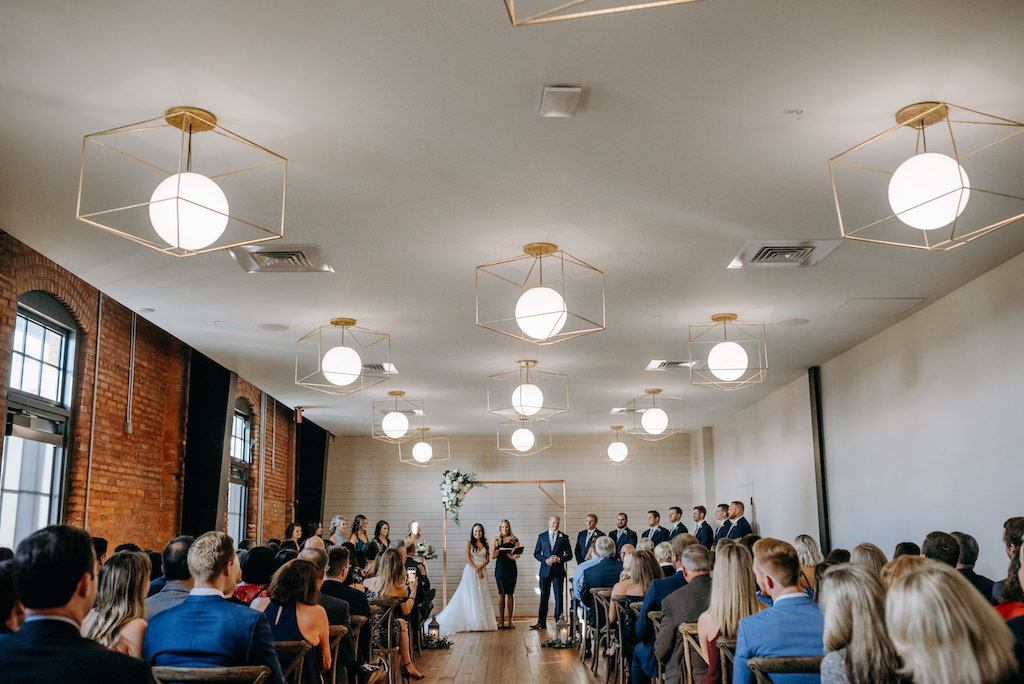 Modern, Geometric Inspired Indoor Navy Wedding Ceremony, Gold Lighting Decor, Exposed Red Brick Wall at The Gathering, Tampa Bay Venue Armature Works