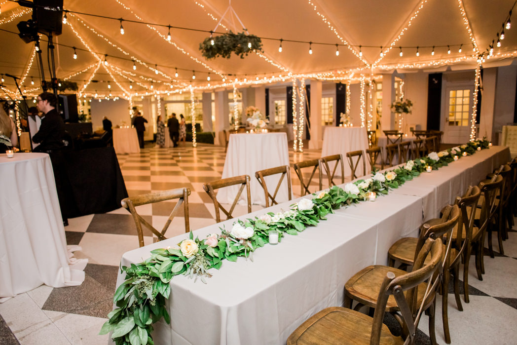 Boho Modern Chic Tent Wedding Reception Decor, Long Feasting Table with Greenery Garland and White, Yellow and Blush Pink Roses, Wooden Crossback Chairs and Tall Cocktail Tables, String Lights | Wedding Venue Tampa Yacht and Country Club