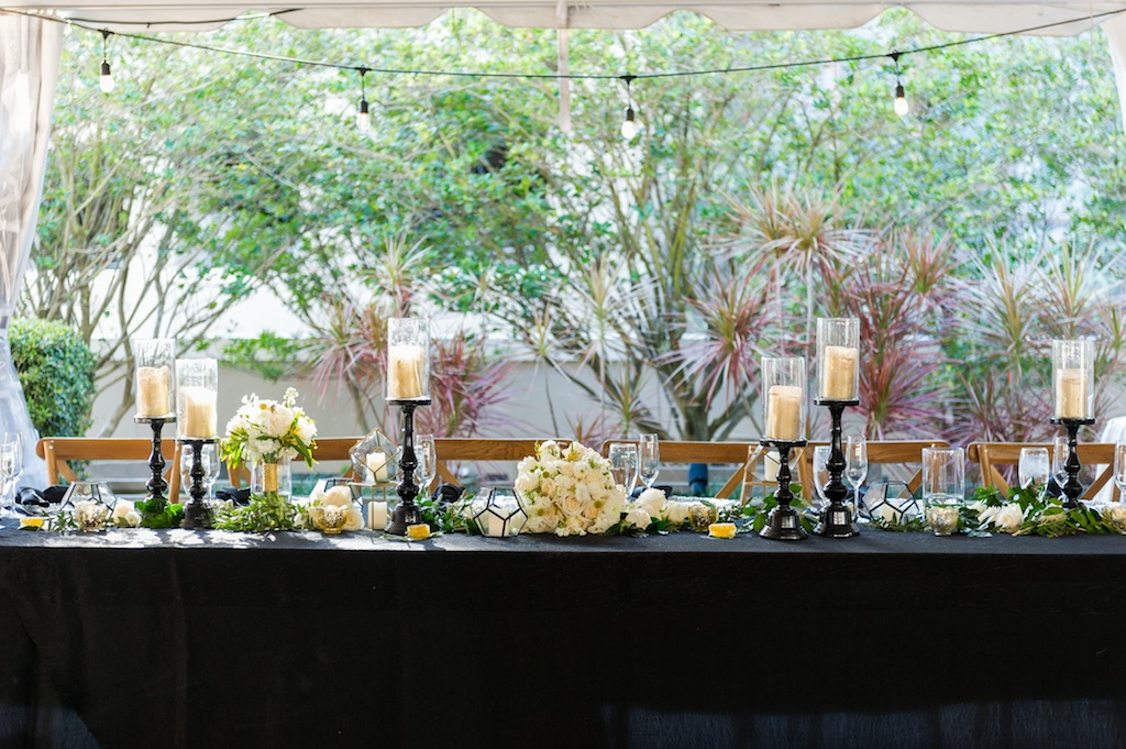 Long Wedding Party Feasting Table, Black Linens,, White, Ivory and Gold Florals, with Greenery, Tall Gold Candles with Black Candlesticks   Historic Hyde Park Wedding Venue Epicurean Hotel in South Tampa   Tampa Bay Wedding Photographer Andi Diamond Photography