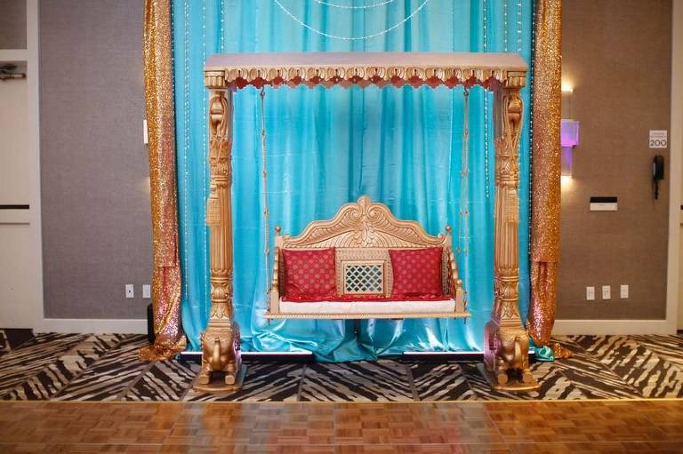 Elegant Traditional Indian Wedding Decor, Gold Arch and Gold Swing Chair with Red Cushions and Blue Satin Backdrop | Hotel Ballroom Wedding Venue Hilton Tampa Airport Westshore