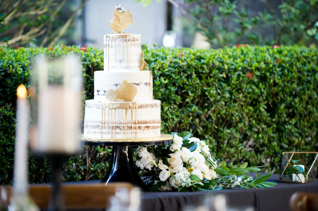 Bumble Bee Honey Inspired, Semi Naked Wedding Cake, White Frosting, Gold Drop and Honeycombs, Next to White, Ivory and Green Floral Arrangement   Historic Hyde Park Wedding Venue Epicurean Hotel in South Tampa   Tampa Bay Wedding Photographer Andi Diamond Photography   Cake Decorator The Artistic Whisk