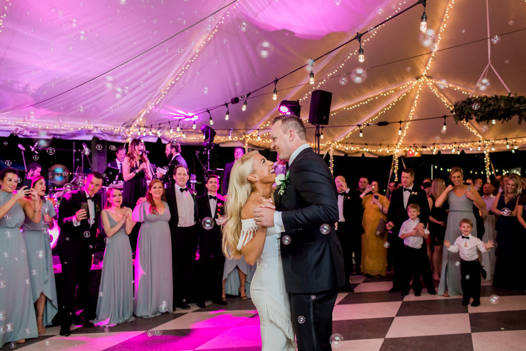 Florida Bride and Groom First Dance Tent Wedding Reception with String Lights and Pink Uplighting Portrait