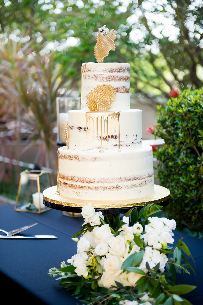 Bumble Bee Inspired, Semi Naked Wedding Cake, White Frosting, Gold Drip and Honeycombs, Next to White, Ivory and Green Floral Arrangement | Historic Hyde Park Wedding Venue Epicurean Hotel in South Tampa | Tampa Bay Wedding Photographer Andi Diamond Photography | Cake Decorator The Artistic Whisk