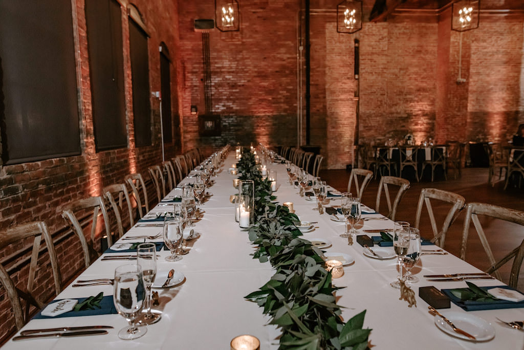Modern, Clean Industrial Wedding Reception Decor, Long Feasting Table with White Linens, Wooden Cross-Back Chairs, Greenery Garland Runner Centerpiece, Sage and Dark Green Linens, Exposed Red Brick   Florida Wedding Venue Armature Works, The Gathering