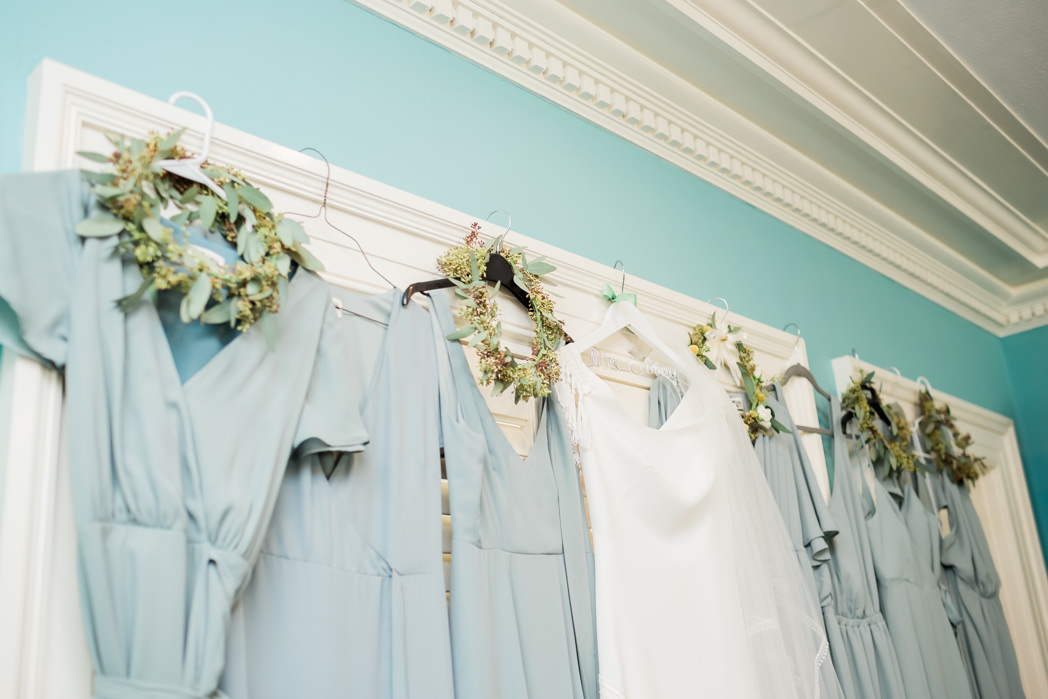 Boho Chic Dusty Blue Bridesmaids Dresses with Greenery Crowns and White Wedding Dress Hanging