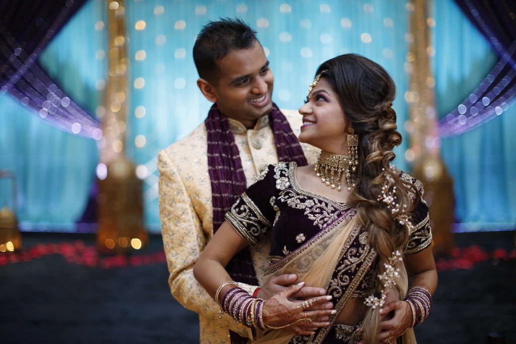 Traditional Indian Bride and Groom Wedding Portrait, Bride in Dark Purple and Gold Sari with Gold Sash and Extravagant Gold Bridal Jewelry and Accessories | Tampa Bay Wedding Hair and Makeup Michele Renee the Studio
