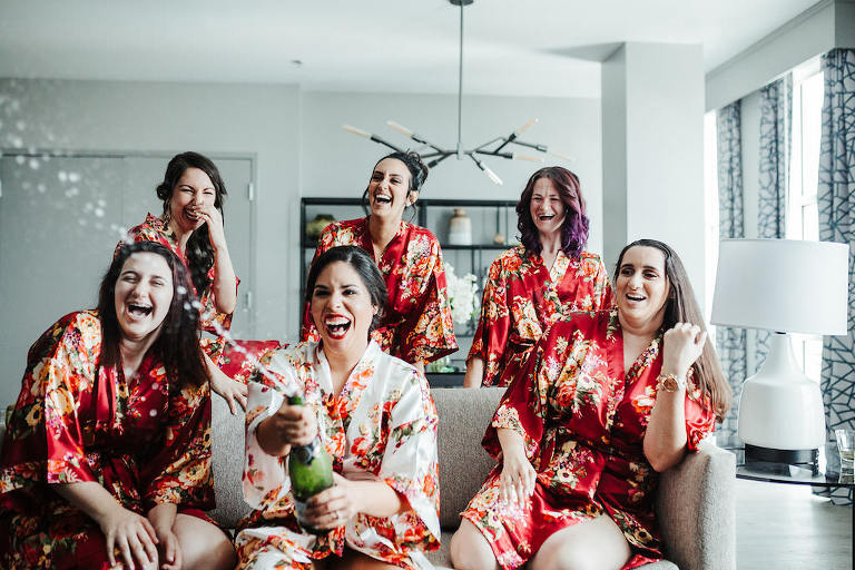 Florida Bride and Bridesmaids Popping Bottles and Champagne, Wearing Matching Red Silk Floral Robes | Tampa Bay Boutique Hotel and Wedding Venue The Hotel Alba in Westshore