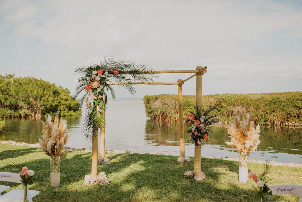 Tropical Destination Florida Outdoor Waterfront Wedding Ceremony with Bamboo Wedding Arch, Wedding Decor with Colorful Flowers, Pink Ginger, King Proteas, Orchids, with Greenery and Pampas Grass | Sarasota Wedding Venue Longboat Key Club