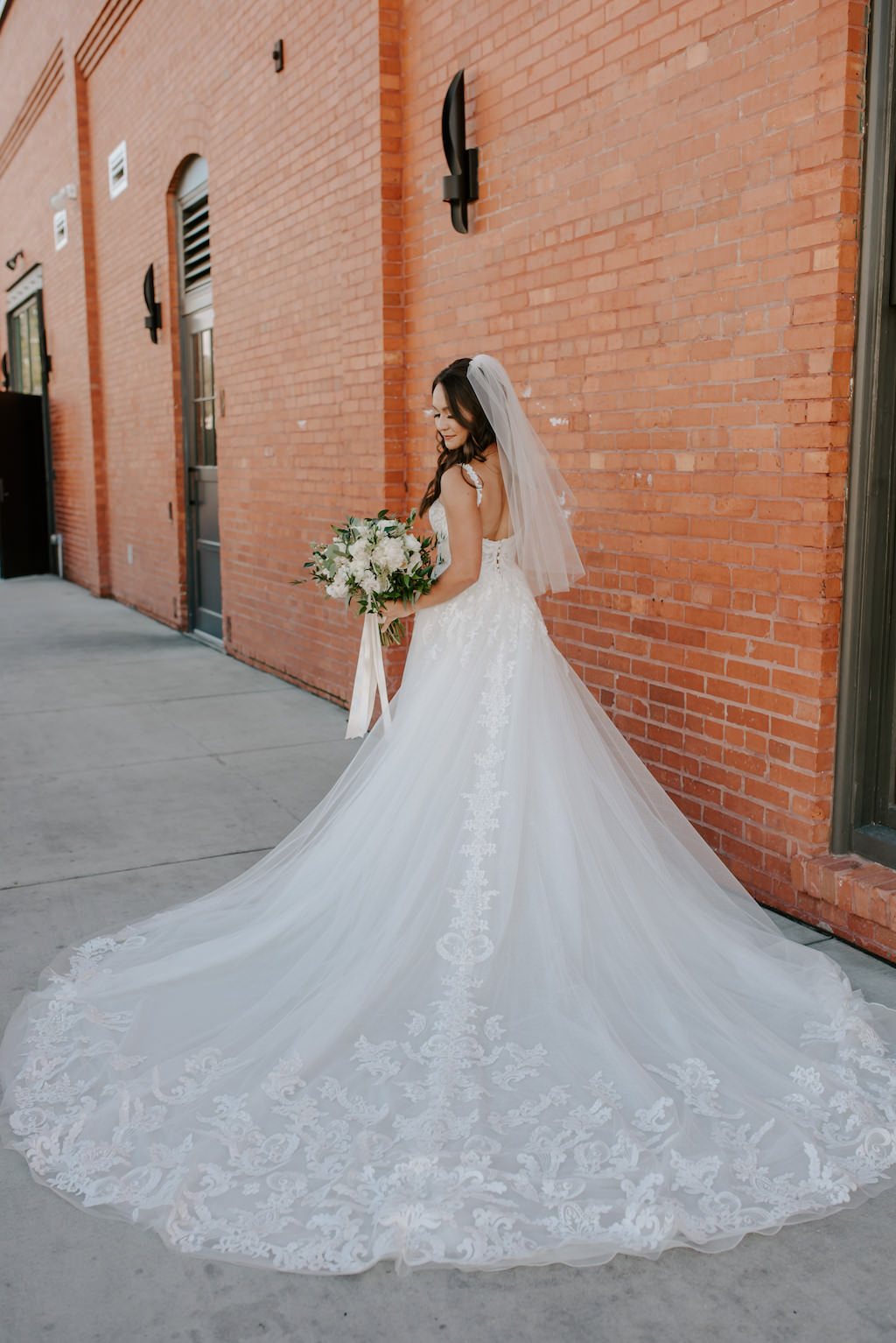 Romantic, Modern Florida Bride in White Essence of Australia Ballgown Style Wedding Dress with Lace Detailing, Red Exposed Brick Wall at Armature Works, The Gathering in Tampa Heights