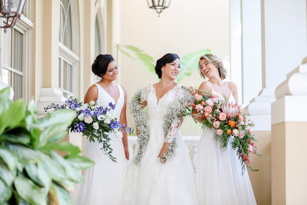 Brides Carrying Unique Floral Wedding Bouquets, Purple Hibiscus, Ivory Carnations, Baby's Breath Garland, Tropical Inspired, Garden Crescent Style Wedding Bouquet with Pink King Protea, Peach, White and Orange Florals with Greenery | Tampa Bay Wedding Photographer Lifelong Photography Studios | Truly Forever Bridal Shop Sarasota