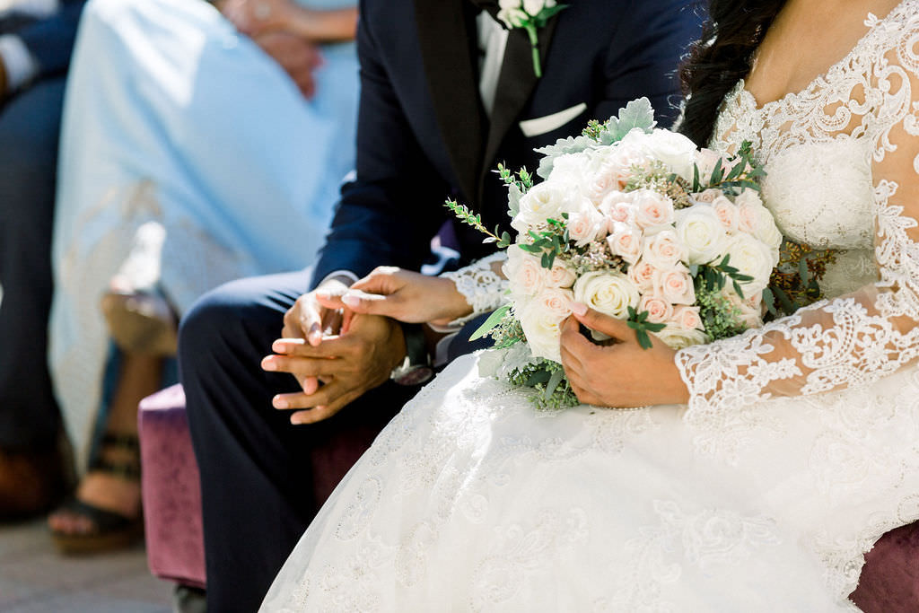 Classic Bride and Groom Hold Hands During Ceremony, Elegant Round Floral Bouquet, Ivory and Blush Pink Roses, Greenery