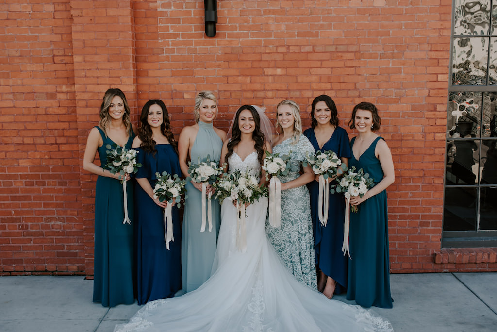 Modern Florida Bride and Bridesmaids, Wearing Mix and Match Navy, Sage, Dark Green and Floral Long Dresses, Organic White and Green Floral Bouquets, Armature Works in Tampa Bay's Wedding Venue The Gathering