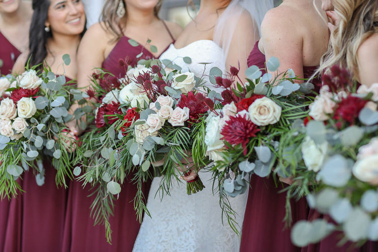 Bride and Bridesmaids in Long Burgundy Wine Red Dresses Holding Garden Style Red, Ivory, and Greenery Floral Bouquets | Tampa Bay Wedding Photographer Lifelong Photography Studios | Tampa Bay Wedding Planner Breezin' Weddings
