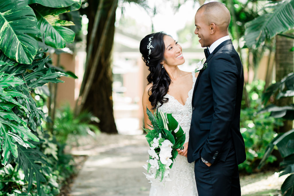 Modern, Tropical Florida Bride and Groom Wedding Portrait with Green and White Bridal Floral Bouquet with Palm Fronds, Monstera leaves and Cascading White Orchids by Tampa Bay Wedding Florist Bruce Wayne Florals | Boho Inspired White Martina Liana Wedding Dress and Loose Curled Side Ponytail Hairstyle with Custom Floral Rhinestone Hairpiece | Florida Resort Waterfront Wedding Venue The Vinoy Renaissance St. Petersburg Resort & Golf Club | Tampa Bay Wedding Hair and Makeup Artist Michele Renee The Studio