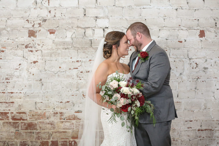 Tampa Bay Groom and Bride in Strapless Lace Fitted Wedding Dress and Cathedral Length Veil with Organic Red, Blush, Ivory and Greenery Floral Bouquet and White Brick Backdrop | Tampa Wedding Photographer Lifelong Photography Studios | Industrial Historic Wedding Venue Rialto Theatre | Tampa Wedding Hair and Makeup Artists Michele Renee the Studio