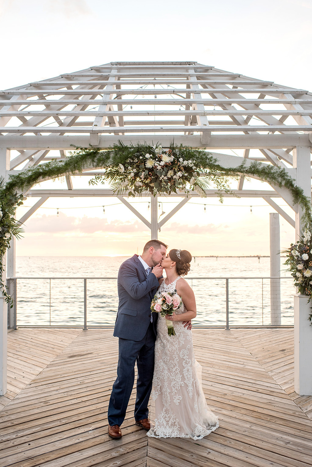Florida Bride and Groom Kiss Portrait, Just Married After Waterfront Dockside Wedding Ceremony Under Cabana, Nautical Inspired Decor, White, Ivory, Blush Pink, and Green Floral Arch | | Tampa Bay Hotel and Wedding Venue The Godfrey Hotel & Cabanas