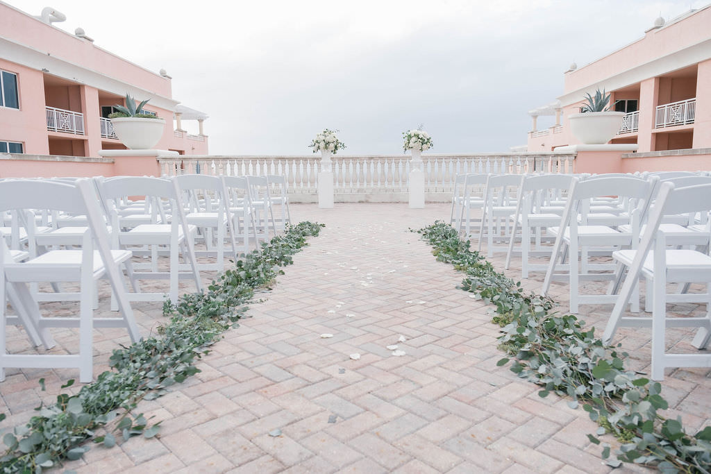 Romantic Boho Chic Inspired Wedding Ceremony Decor, White Folding Chairs, Silver Dollar Eucalyptus Greenery Aisle Decor, White Pedestals with White and Greenery Floral Bouquets   Planner Parties A'la Carte   Florist Bruce Wayne Florals   Waterfront Tampa Bay Hotel Venue Hyatt Regency Clearwater Beach