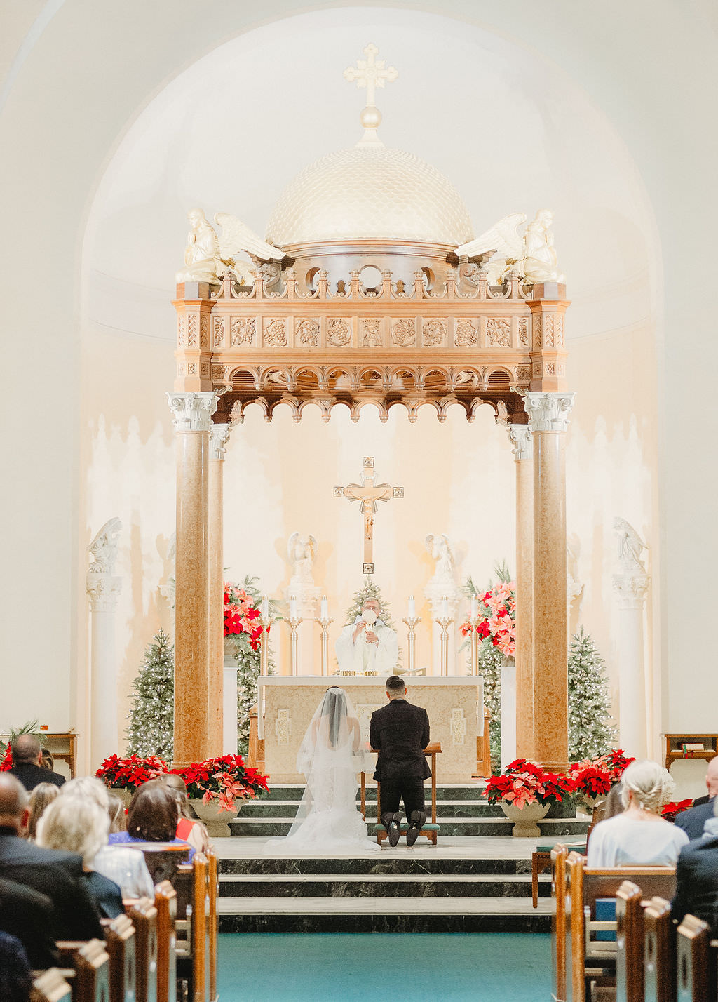Florida Bride and Groom During Traditional Catholic Church Wedding Ceremony Kneeling at Altar