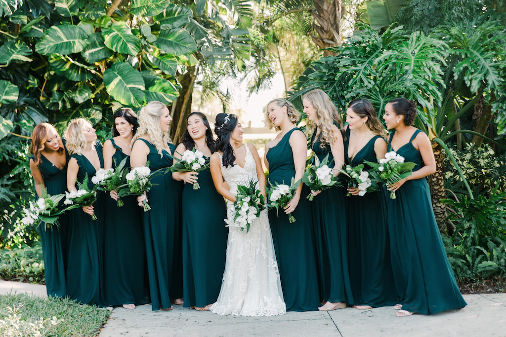 St. Pete Bridal Party Bridesmaids in Modern Long Dark Green Monique Lhuillier Bridesmaid Dresses from Bella Bridesmaids, Carrying White Orchid and Green Palm Leaf Bouquet, Boho Bride in Martina Liana Wedding Dress with Straps and V Neckline | Tampa Bay Florist Bruce Wayne Florals | Waterfront Hotel Wedding Venue The Vinoy Renaissance | Hair and Makeup Artist Michele Renee The Studio