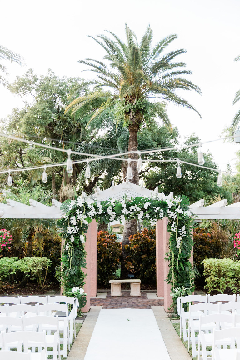 Romantic, Modern, Tropical Wedding Decor, Ceremony Arch with Monstera Leaves, Green Palm Fronds, White Orchids, Hanging Lights | The Tea Garden at The Vinoy Renaissance St. Petersburg Resort & Golf Club | Tampa Bay Florist Bruce Wayne Florals Florida Luxury Wedding Planner Parties A'La Carte