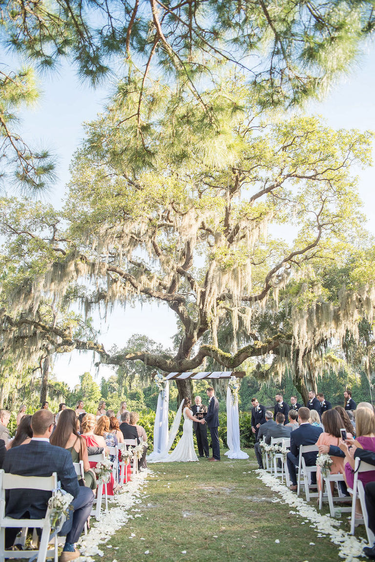 Florida Bride and Groom Exchanging Vows Under Wooden Arch with White Draping and Blue and White Flower Bouquets on Golf Course Wedding Ceremony Portrait | Tampa Bay Wedding Photographer Kristen Marie Photography | Innisbrook Golf & Spa Resort Wedding Venue