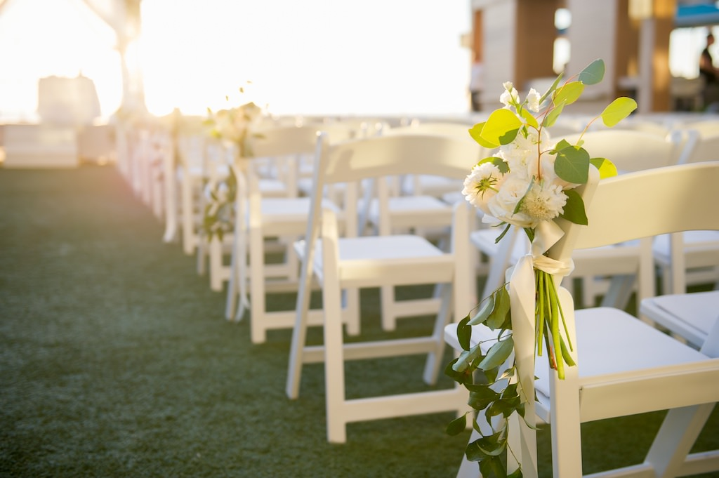 Outdoor Clearwater Beach Lawn Wedding Ceremony | White Garden Chairs with Greenery Inspired Flowers