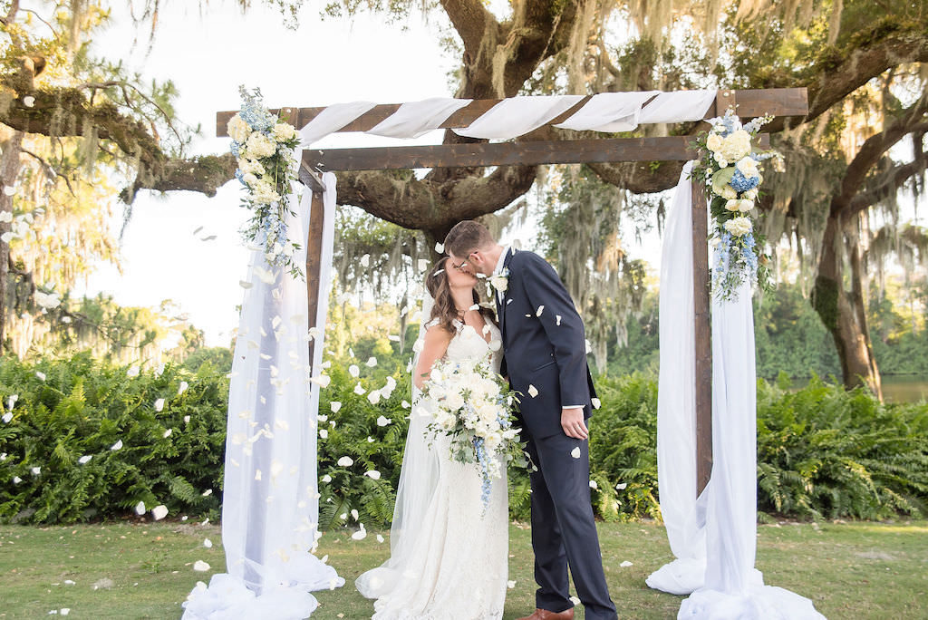 Palm Harbor Bride and Groom Kissing Wedding Portrait Under Wooden Ceremony Arch with White Draping and Ivory and Blue Flower Bouquets with White Flower Petals Blowing in the Wind | Tampa Bay Wedding Photographer Kristen Marie Photography | Innisbrook Golf & Spa Resort Wedding Venue