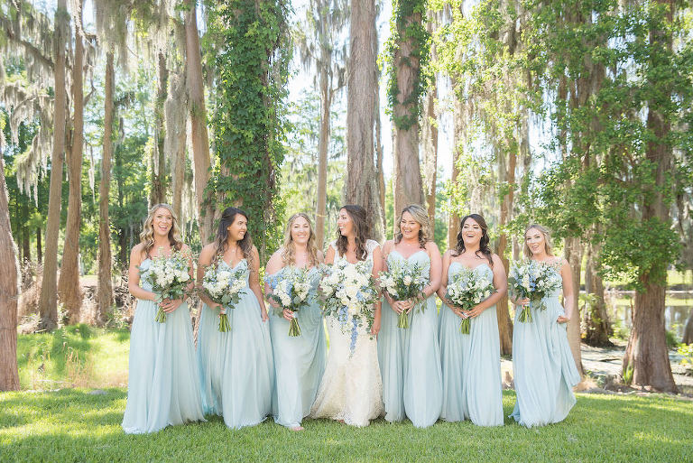 Palm Harbor Bride and Bridesmaids Outdoor Portrait, Bridesmaids in Flowy Classic Boho Long Powder Blue Dresses Holding White, Ivory, and Greenery Floral Bouquets | Tampa Bay Wedding Photographer Kristen Marie Photography | Innisbrook Golf & Spa Resort Wedding Venue | Destiny and Light Hair and Makeup Group | Palm Harbor Bridesmaid Dress Shop Nikki's Glitz and Glam