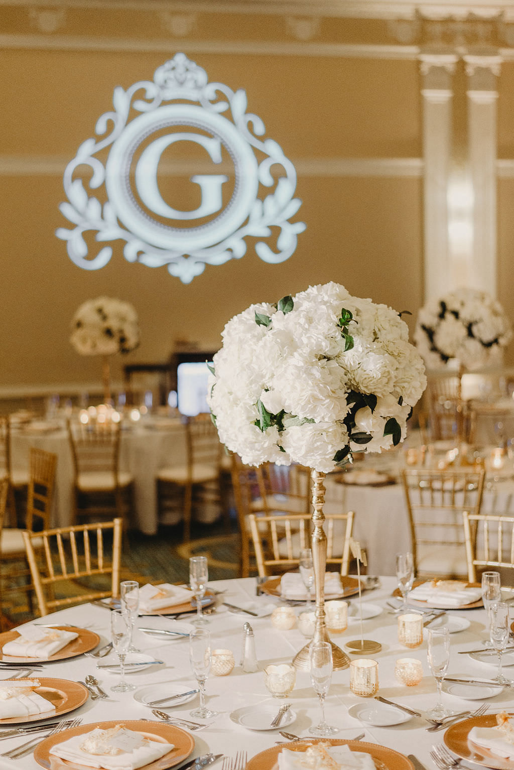 Traditional Classic Ballroom Wedding Reception Decor, Round Tables with White Tablecloths, Gold Chargers, Tall Gold Vase with Round White Floral Centerpiece, Custom Gobo Monogram Projection   St. Pete Hotel Ballroom Wedding Venue The Vinoy Renaissance