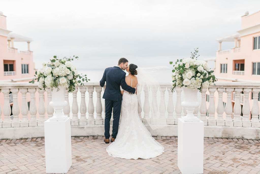 Florida Bride and Groom Intimate Wedding Portrait on Rooftop Terrace, White Pedestals with White, Ivory and Greenery Floral Bouquets   Waterfront Hotel Wedding Venue Hyatt Regency Clearwater Beach   Tampa Bay Rooftop Wedding Ceremony   Florist Bruce Wayne Florals   Planner Parties A'la Carte