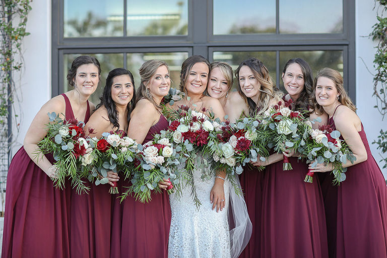 Bride and Bridesmaids in Long Burgundy Wine Red Dresses Holding Garden Style Red, Ivory, and Greenery Floral Bouquets | Tampa Bay Wedding Photographer Lifelong Photography Studios | Tampa Bay Wedding Planner Breezin' Weddings | Tampa Bay Hair and Makeup Team Michele Renee the Studio