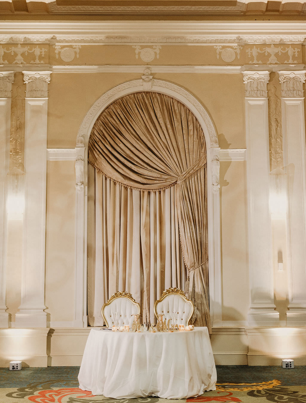 Classic Traditional Ballroom Wedding Reception Decor, Sweetheart Table with White Tablecloth, Fancy Gold and Ivory High Back Chairs and Champagne Gold Draping Background   St. Pete Hotel Wedding Venue The Vinoy Renaissance