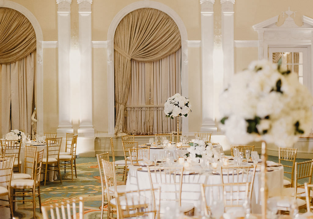 Classic, Timeless Traditional Ballroom Wedding Reception Decor, Round Tables with White Tablecloths, Gold Chiavari Chairs, Tall Gold Vases with Round White Floral Centerpieces   Luxurious St. Pete Hotel Ballroom Wedding Venue The Vinoy Renaissance