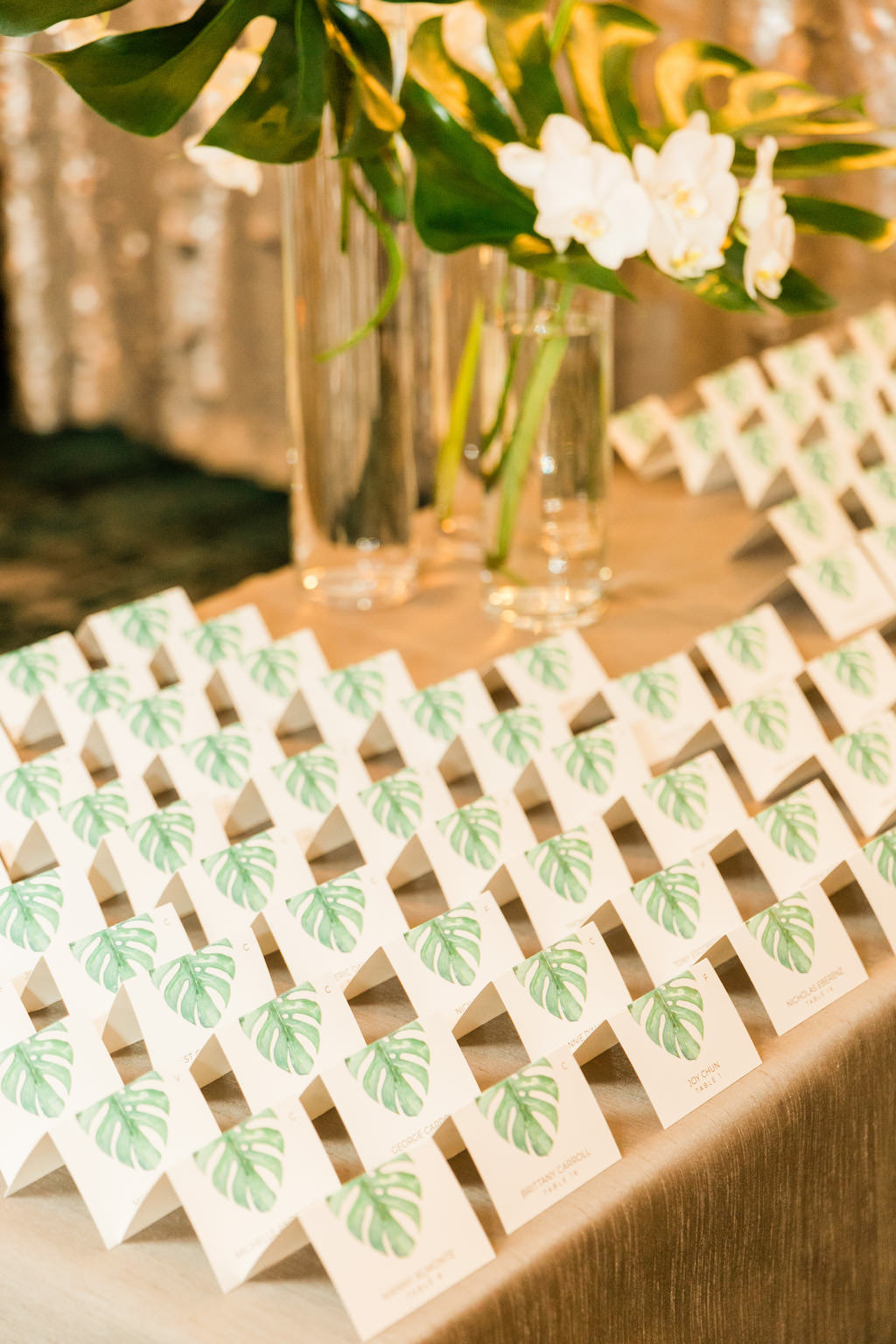 Tropical Inspired, Modern Florida Wedding Reception Decor, Green Monstera Leaf Escort Seating Card with White Orchid Florals | Tampa Bay Invitation and Wedding Suite Designer URBANCoast | Florida Luxury Wedding Planner Parties A'La Carte
