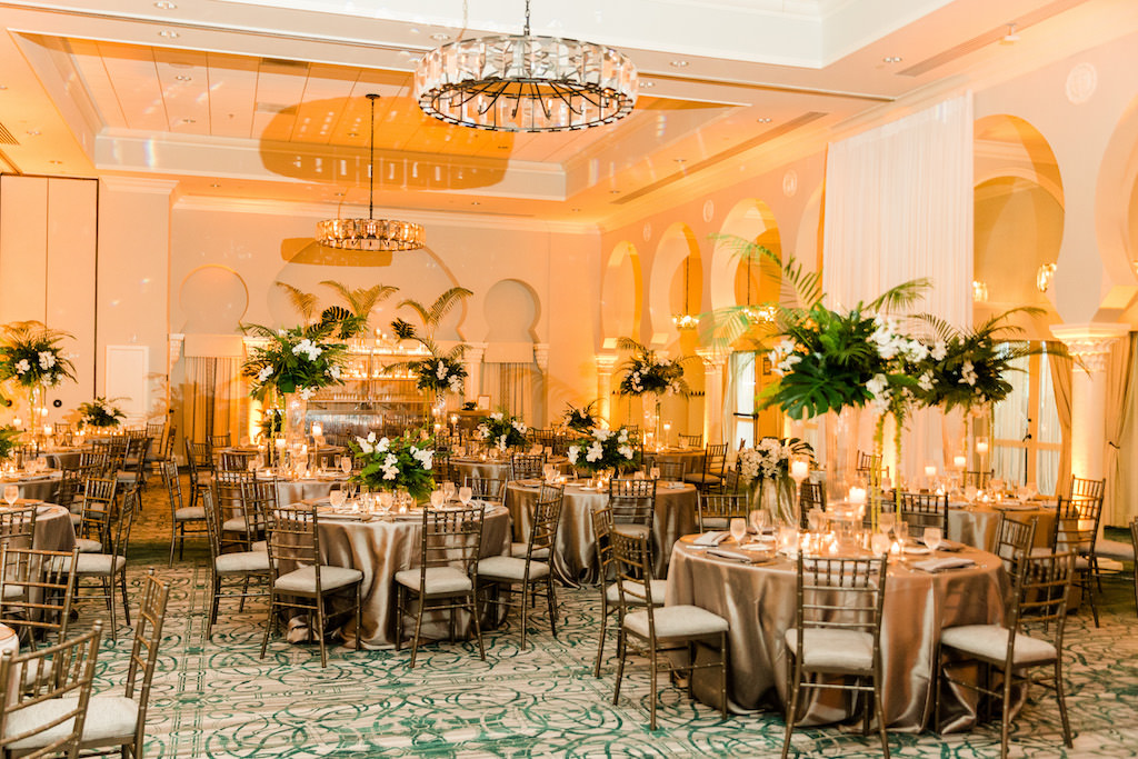 Tropical Florida Inspired Wedding Reception, Modern Wedding Decor, Tall Floral Centerpieces with Green Monstera Leaves, Large Palm Fronds, White Orchids, Round Tables with Silver Linens, Chiavari Chairs, Grand Ballroom of The Vinoy Renaissance St. Petersburg Resort & Golf Club | Over the Top Rental Linens | Tampa Bay Florist Bruce Wayne Florals | Florida Luxury Wedding Planner Parties A'La Carte