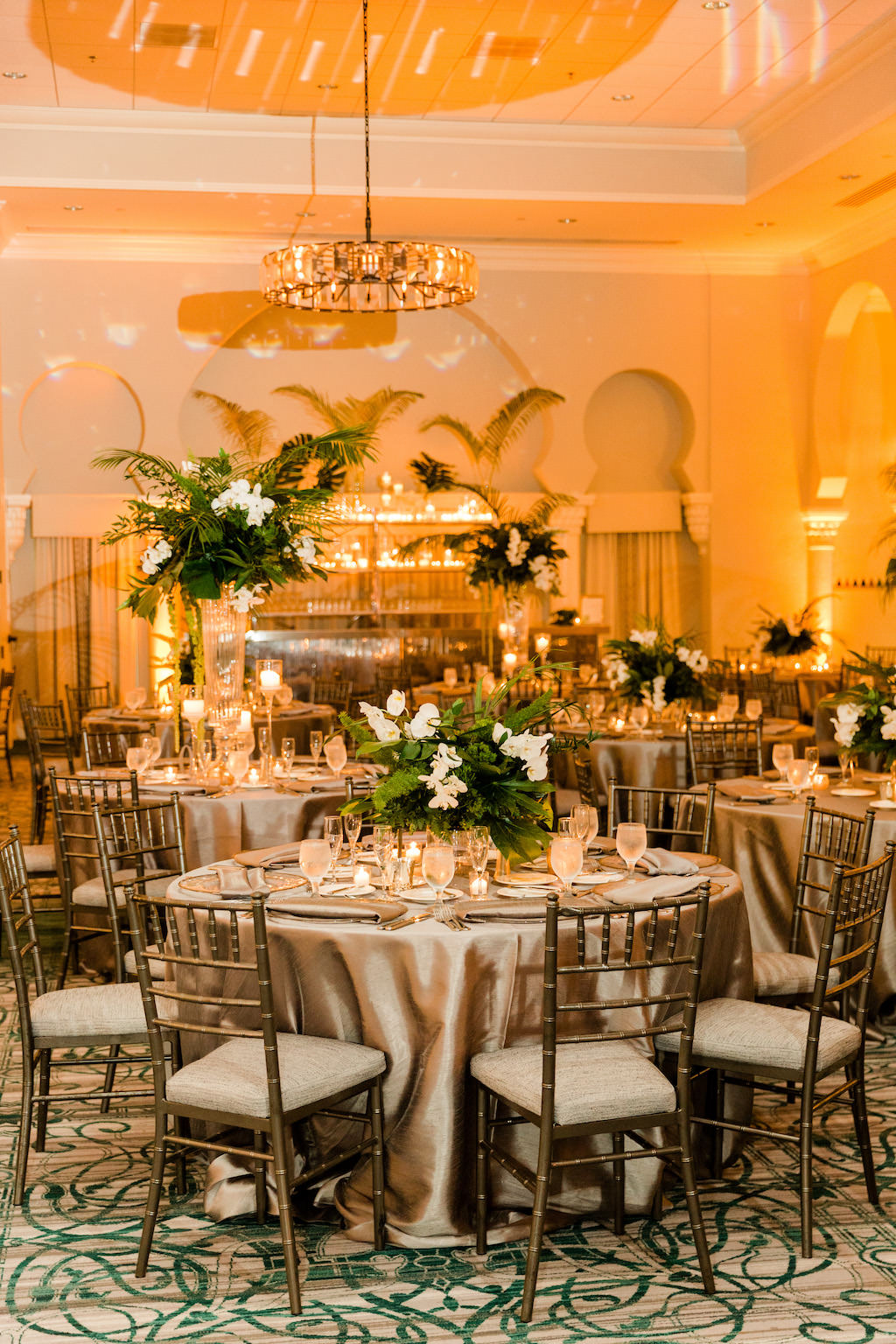 Tropical Florida Inspired Wedding Reception, Modern Wedding Decor, Tall and Low Mix Match Floral Centerpieces with Green Monstera Leaves, Large Palm Fronds, White Orchids, Round Tables with Silver Linens, Chiavari Chairs, Grand Ballroom of The Vinoy Renaissance St. Petersburg Resort & Golf Club | Over the Top Rental Linens | Tampa Bay Florist Bruce Wayne Florals | Florida Luxury Wedding Planner Parties A'La Carte