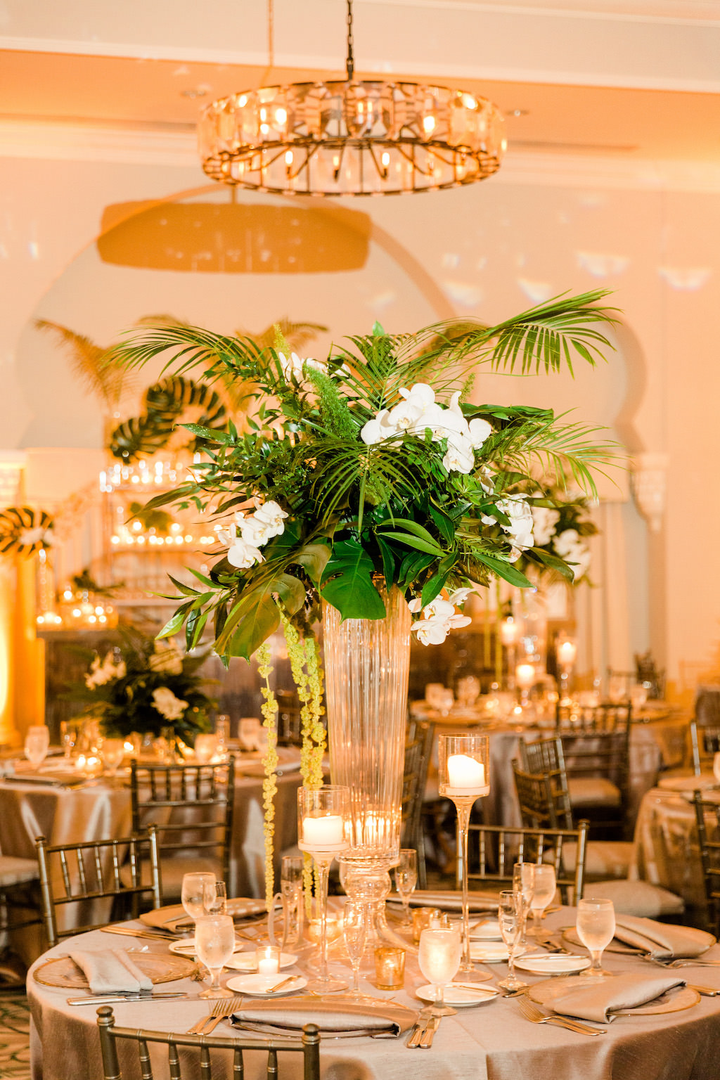 Tropical Inspired, Modern Wedding Reception Decor, Tall Centerpieces with Green Monstera Leaves, Large Palm Fronds, White Orchid Florals, Hanging Green Amaranthus, Round Tables with Silver Linens, Chiavari Chairs, Grand Ballroom of The Vinoy Renaissance St. Petersburg Resort & Golf Club | Over the Top Rental Linens | Tampa Bay Florist Bruce Wayne Florals | Florida Luxury Wedding Planner Parties A'La Carte