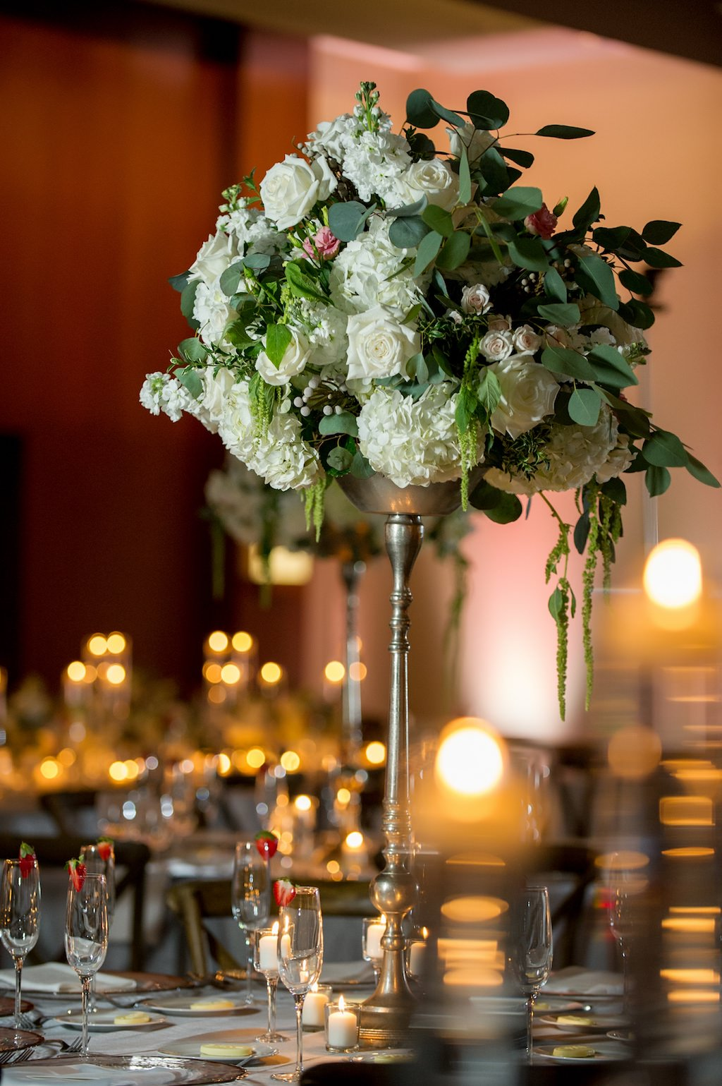 Elegant, Romantic Ballroom Wedding Reception with Long Feasting Tables, Low White Centerpieces, and Candles