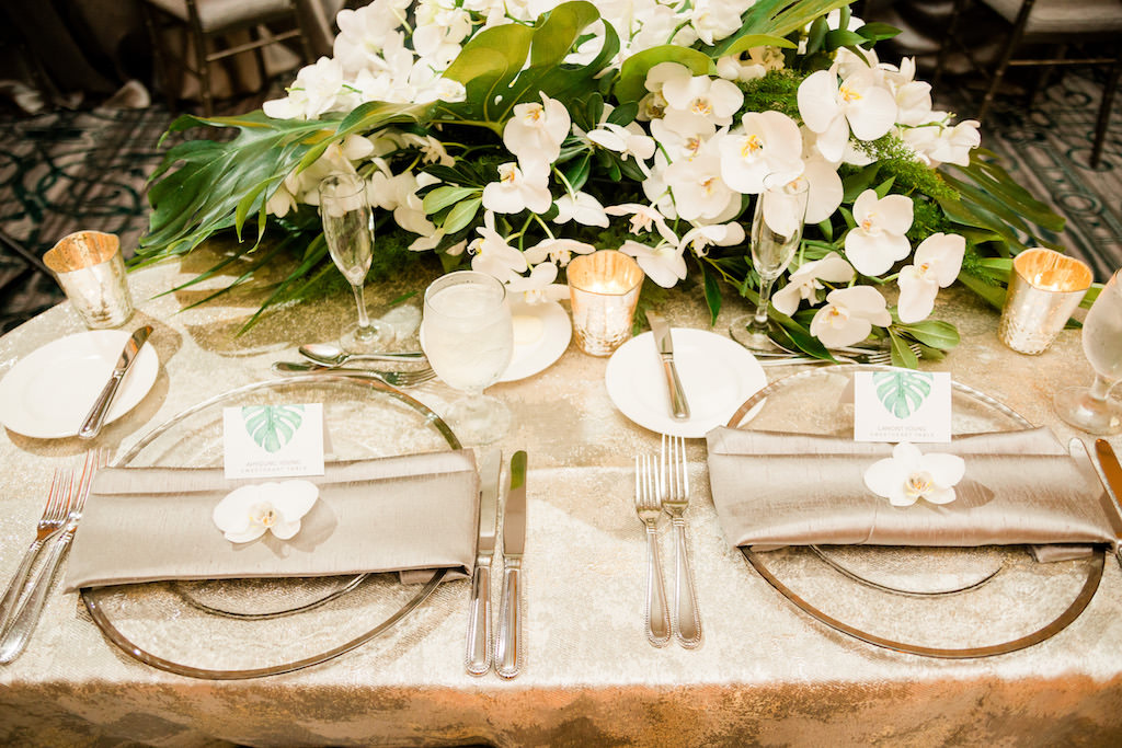 Tropical Inspired, Modern Wedding Reception Decor, Silver Accented Sweetheart Table Linens with Green Monstera Leaves and Lush Cascading White Orchids, Clear Glass and Silver Rimmed Chargers | Over the Top Rental Linens | Tampa Bay Florist Bruce Wayne Florals | Florida Luxury Wedding Planner Parties A'La Carte | Place Cards by URBANCoast
