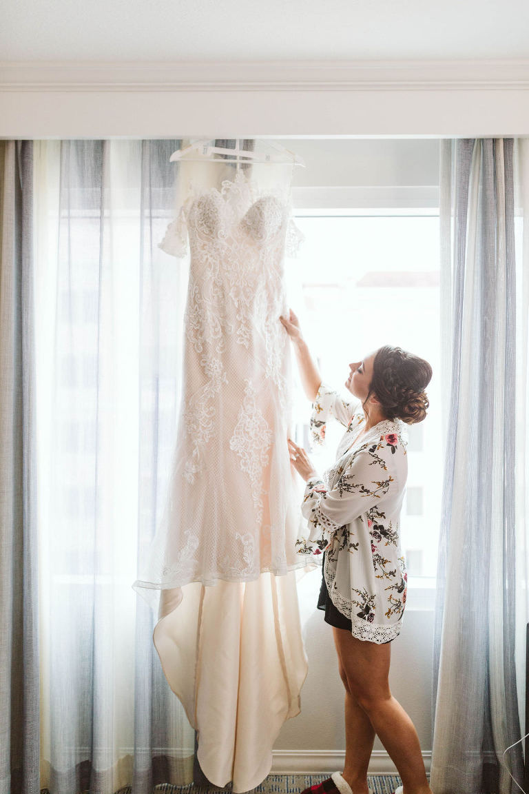 Florida Bride Getting Ready Wedding Portrait in White Floral Robe Looking at Lace Fitted Off the Shoulder Illusion Neckline Wedding Dress